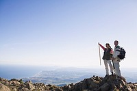 Senior couple standing on cliff with backpacks