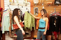 Two Hispanic women looking at clothing in boutique