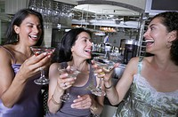 Portrait of Hispanic women toasting at bar