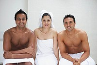 Two men and a woman in towels sitting on bench in bathroom