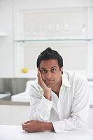 Middle Eastern man leaning on counter in kitchen