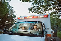 Male and female paramedics in cab of ambulance
