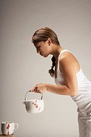 Pacific Islander woman holding teapot over teacup