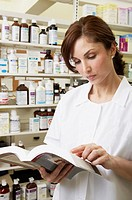 Female pharmacist looking at book in pharmacy