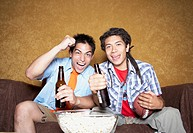 Two young men cheering on sofa with football