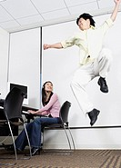 Asian man jumping next to Asian female computer service technician