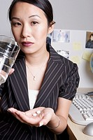 Asian businesswoman taking medication at desk