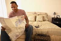 African man sitting on bed looking at map