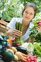 Young woman with asparagus and radishes