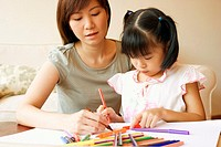 Close-up of a young woman teaching her daughter to color