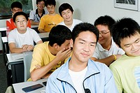 Group of teenage boys sitting in a classroom and smiling