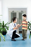 Male doctor crouching with a boy standing beside him