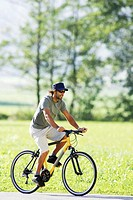 Germany, Bavaria, man riding bicycle, side view