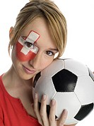 Woman with Swiss flag painted on face, holding football, close-up, portrait