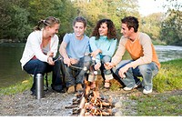 Teenagers 16-19 sitting around fire by river, smiling