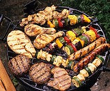 Vegetables, meatballs, fish, poultry and sausages on grill