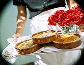 Hands holding tray with Crema catalana and carnations 1
