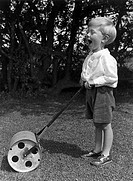 Small boy with a garden roller, c 1930s  Boy with a toy grass roller