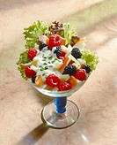 Shrimp salad with berries in glass bowl