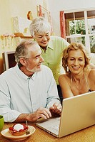 Mature couple and a senior woman smiling in front of a laptop
