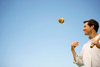 Low angle view of a mid adult man tossing a ball