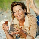 Portrait of a mature woman lying on the beach and holding a champagne flute