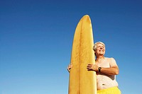 Low angle view of a mature man holding a surfboard