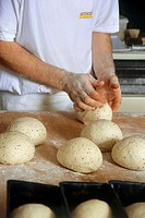 Baker shaping bread rolls