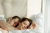 Young couple sleeping and cuddling in bed together