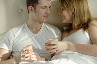 Young couple in bed having coffee together
