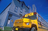 A school bus parked in front of an old building