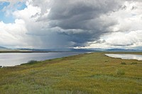 Storm clouds over grasslands and mountains