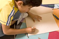 Portrait of Hispanic boy drawing