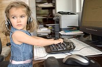 Portrait of a little blonde girl working on the computer
