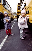 Two young girl poses in front of a school bus