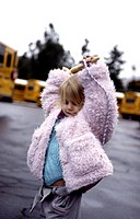 A young girl dances in front of a school bus