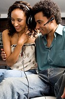 Portrait of a couple cuddling wearing headphones and ear pieces