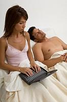 Portrait of woman using her laptop in bed while her husband sleeps