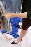 Woman in her 20's looking through a clothes rack stepping on a piece of clothing falling on the floor