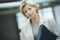 Businesswoman holding laptop, portrait