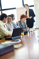 Group of businesspeople sitting around conference table during presentation