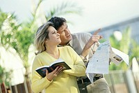 Mature couple standing outdoors with map and guidebook, man pointing