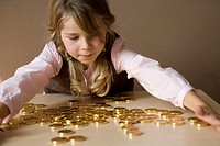 little girl with many gold coins on table