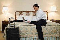 Businessman in Hotel Room Using Laptop