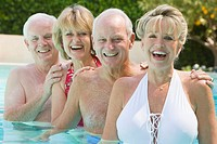 Two Senior Couples Relaxing in Swimming Pool
