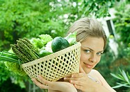 Woman holding basket full of fresh vegetables, smiling at camera
