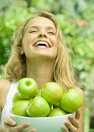 Woman holding bowl of apples, laughing