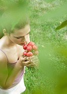 Woman smelling bunch of radishes