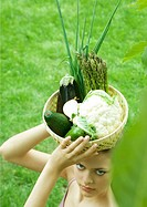Woman holding basket full of fresh vegetables on top of head