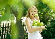 Woman holding bowl of apples, holding one up to mouth, smiling at camera
